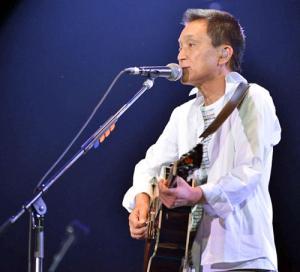 ライブで熱唱する小田和正
